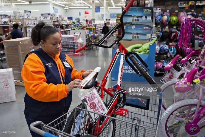 An employee tags an item for store pickup, a program where customers select and pay for items online for pickup, at a Wal-Mart Stores Inc. location in Chicago, Illinois, U.S., on Wednesday, Nov. 25, 2015. In 2011, several big U.S. retailers moved their opening times to midnight; in 2012, Wal-Mart crossed the Rubicon and opened its stores at 8 p.m. on Thanksgiving Day. But after last year's Thanksgiving weekend retail sales fell 11 percent from the year before while overall holiday sales rose, some retailers have been reconsidering. Photographer: Daniel Acker/Bloomberg