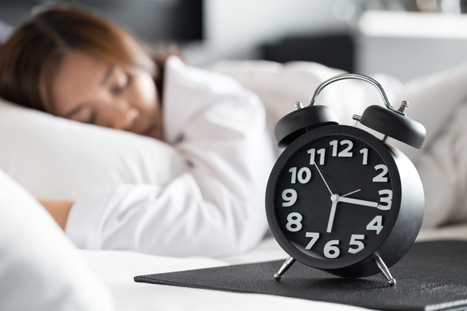 woman sleeping on bed and wake up with alarm clock