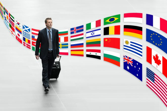 businessman traveling with trolley international flags trip traveler or passenger